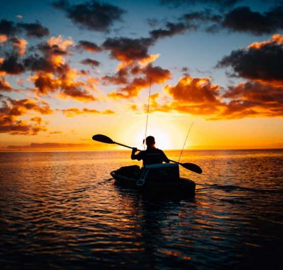 man in kayak at sunrise paddling in water