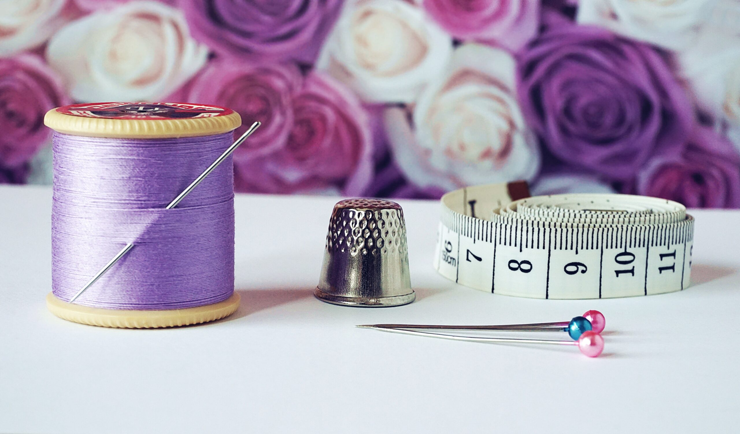 spool-of-purple-thread-needle-thimble